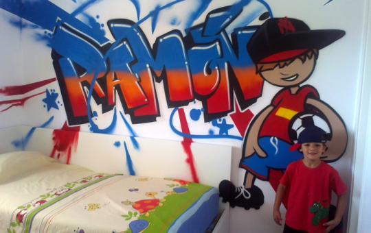 Ramón posando junto al graffiti de su habitación