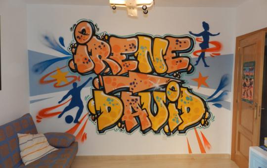 Fotografía del graffiti de los nombres de Irene y David en su habitación de juegos.