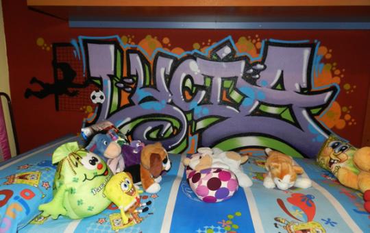 Graffiti con el nombre de Lucía en pared de habitación juvenil